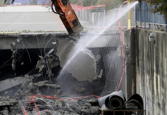Another chunk of concrete falls as an excavator caves in the northern part of the downtown Redding parking structure on Tuesday, Nov. 26, 2019. Water is being spraying on the demolition work to keep the dust down.