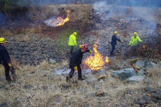 The Redding Fire Fuel Crew burns off piles of tree and brush limbs left over from thinning projects conducted last summer and earlier this fall.