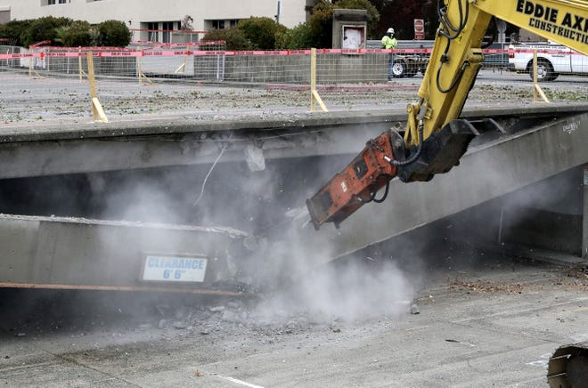 The first concrete beam comes crashing down at the downtown parking garage on Tuesday, Nov. 26, 2019, as an excavator operator with Axner Excavating begins the demolition of the lot's northern section.