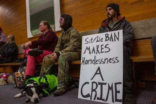 A man silently protests during a City Council meeting on Nov. 25 in downtown Salem. The city took a preliminary vote not to ban the people from sitting and lying on public sidewalks, on Monday night.