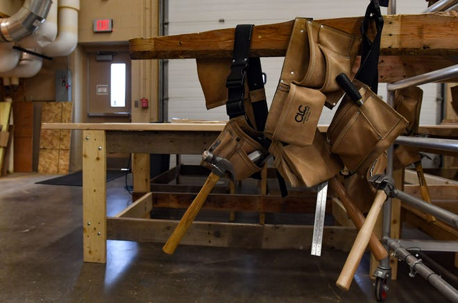 Hammers hang from tool belts on Tuesday, Nov. 26, in the Harrisburg High School wood shop.