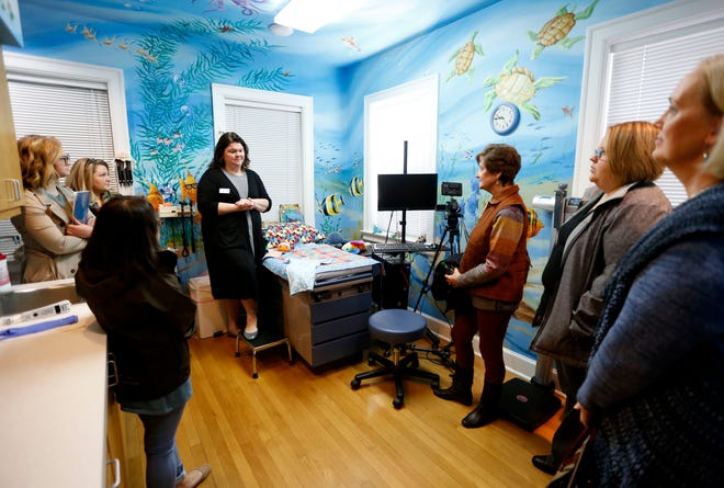 """Amy Hathcock, with the Child Advocacy Center, talks to participants of the """"Journey Home"""" bus tour about the exam procedure on Monday, Nov. 25, 2019. Kids who come to the Child Advocacy Center are givencomprehensive, head-to-toe physical exams used to document recent or past trauma."""