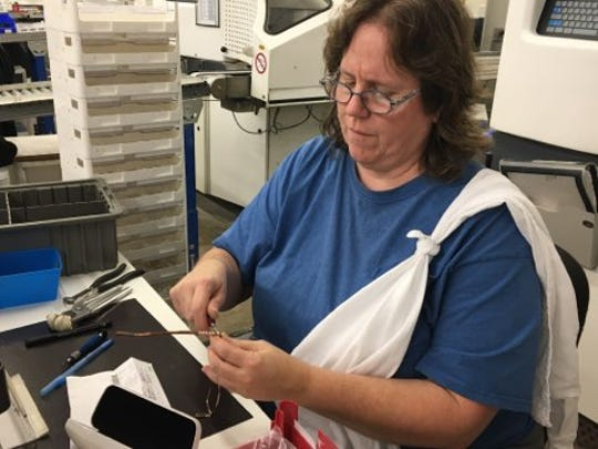 Linda Gertken inserts lenses into eyeglass frames Thursday at Precision Optics after they've been cut to the proper size.