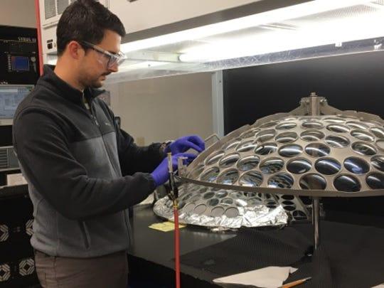 Ismael Fernandez applies a reflective coating to lenses at Precision Optics Thursday.