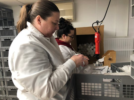 Jennifer Moreno, foreground, and Fran Hernandez fill canisters at Microbiologics Monday.