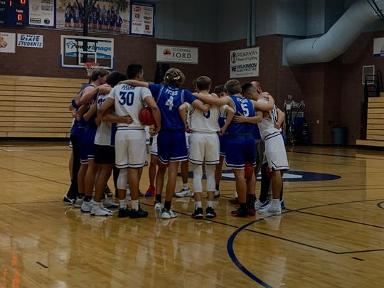 Dixie High's boys basketball team huddles during an inter-squad scrimmage.