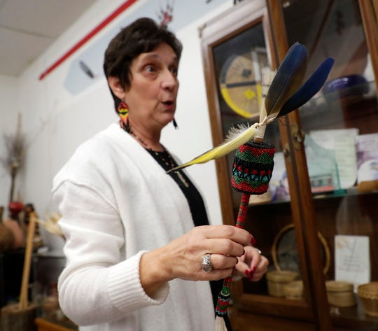 Marian McCormick, Principal Chief of the Lower Muskogee Creek Tribe, shakes a rattle made by tribal member.