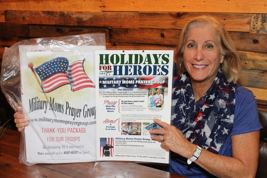 "Linda Colontrelle, president of the Military Moms Prayer Group, holds a sample mailing kit for the group's 2019 Holidays for Heroes program.  ""We want our troops to know that they are not forgotten,"" said Colontrelle."