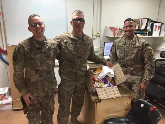 """Soldiers in Afghanistan show off packages received from St. Paul's Church teens and middle school students through the Military Moms Prayer Group's """"Holidays for Heroes"""" gift drive. The Vero Beach church is one of many venues serving as a pick-up location for mailing kits that offer how-to instructions on sending packages to U.S. troops."""