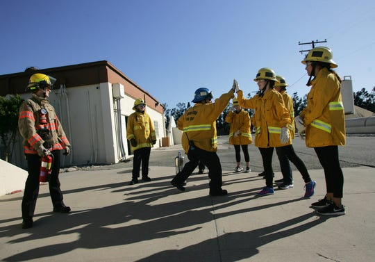 Instructor Brenda Pasqua gives a high-five to student Hannah Wetherell for correctly answering a question about extinguishing a fire on Nov. 23, 2019 during a two-day girls' fire camp at the Camarillo Airport.