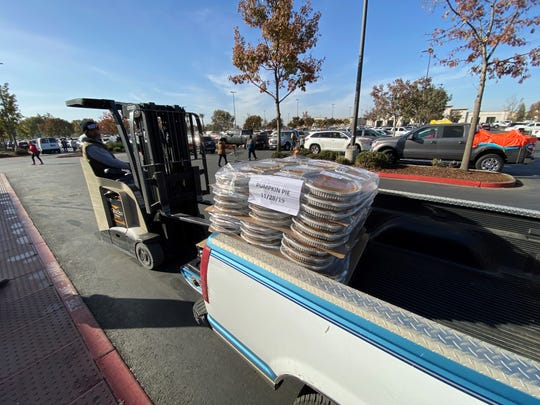 A Visalia Costco employee loaded dozens of pumpkin pies in the back of a member's truck, minutes after the store opened on Tuesday, November 26, 2019.