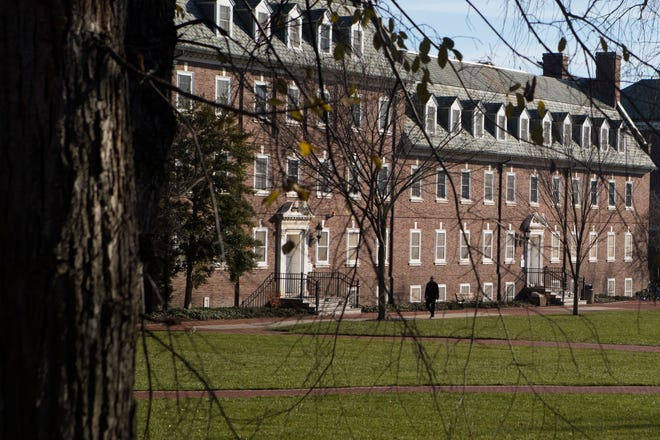A person walks along the green at the University of Delaware next to Main Street in Newark.