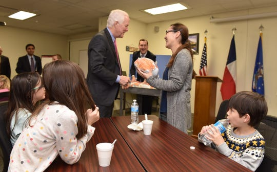 U.S. Sen. John Cornyn, R-Texas, gives a turkey to the family of a deployed service member during a visit to Sheppard Air Force Base Tuesday ahead of Thanksgiving.