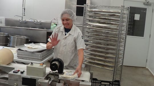 Carol Gitto loads packaged tortillas onto a tray at the end of the assembly line.