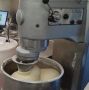 A batch of dough is mixed by a commercial mixer.