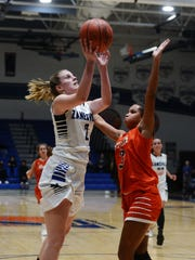 Madison Winland goes up for a shot over Heath's Taliyah Holmes during the second quarter of Zanesville's 50-37 win on Monday night at Winland Memorial Gymnasium.