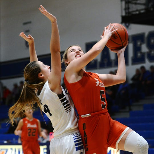 Heath's Cassidy Dupps goes up for a shot over Zanesville's Emmah Kronenbitter on Monday night at Winland Memorial Gymnasium. Zanesville won, 50-37.