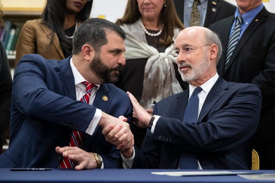 Pennsylvania Gov. Tom Wolf, right, shakes hands with Rep. Mark Rozzi, D-Berks, after signing legislation into law at Muhlenberg High School in Reading, Pa., Tuesday, Nov. 26, 2019. Wolf approved legislation Tuesday to give future victims of child sexual abuse more time to file lawsuits and to end time limits for police to file criminal charges.