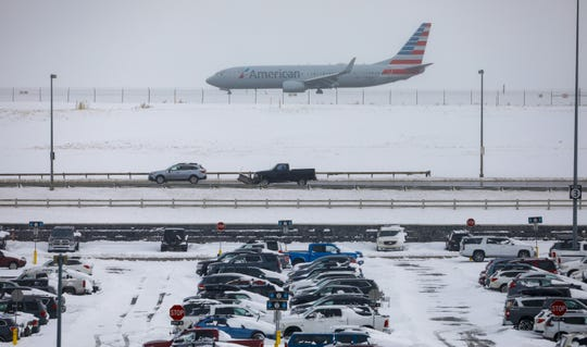 A jet passes snow-covered cars parked at Denver International Airport on Nov. 26, 2019, in Denver. Flights were delayed and rescheduled due to a winter storm that dropped nearly a foot of snow in the city.