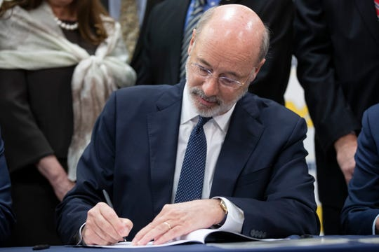 Pennsylvania Gov. Tom Wolf signs legislation into law at Muhlenberg High School in Reading, Pa., Tuesday, Nov. 26, 2019.