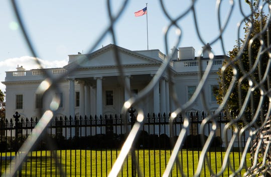 The White House sits behind a fence as construction of the inaugural parade presidential fence in November of 2016.