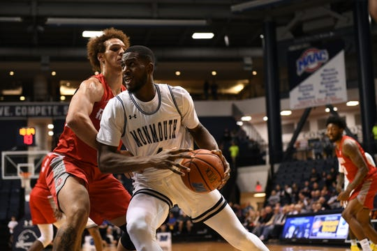 Monmouth forward Mustapha Traore drives to the basket against Radford's Lewis Djonkam on Tuesday night at OceanFirst Bank Center in West Long Branch.