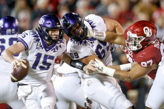 TCU quarterback Max Duggan (15) scramble s away as TCU center Coy McMillon (69) gets pushed back by Oklahoma defensive lineman Marquise Overton (97) during their game Saturday, Nov. 23, 2019, in Norman, Okla.