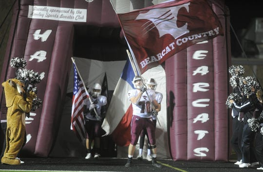 Hawley senior lineman Colton Strickland waves a Bearcats flag before an area playoff against New Deal.