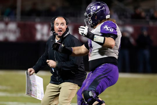 Abilene Christian head coach Adam Dorrel, left, and offensive lineman Jon Crisp (68) body-bump following their team's only point-after attempt during the first half against Mississippi State on Nov. 23 in Starkville, Miss. Mississippi State won 45-7.