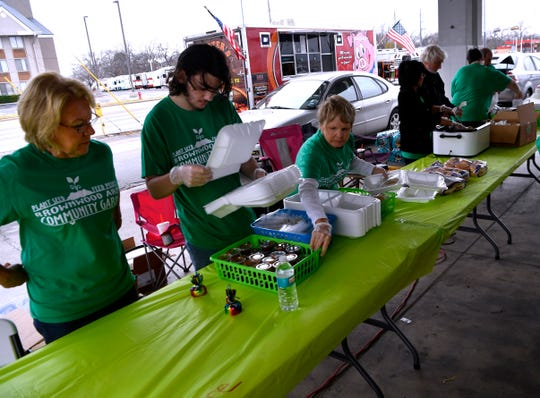 Volunteers for Brownwood Area Community Garden serve barbecue sandwiches during a fundraiser for the garden Nov. 21.
