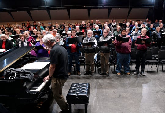 The combined choirs of seven churches practice Nov. 21 at the Abilene Convention Center, led by Abilene Philharmonic conductor David Itkin.