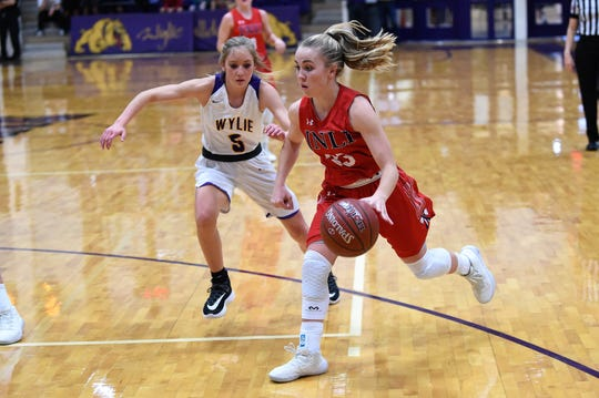 Jim Ned's Brooke Galvin (33) drives past Wylie's Morgan Travis (5) at Bulldog Gym on Tuesday, Nov. 26, 2019. The Galvin scored a team-high 14 points in the 42-41 loss.