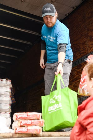 Clay Parker, a volunteer from Duke Energy, helps pack bags of food with Ingles employees November 27, 2019 at the South Forest Shopping Center. More than 13,000 meals were distributed to clients of Eblen Charities.