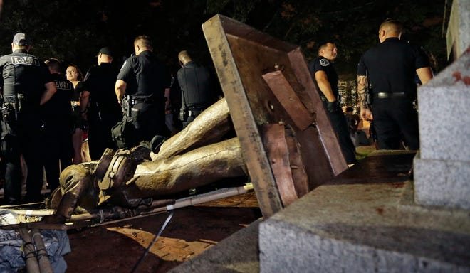 """In this Aug. 20, 2018, file photo, police stand guard after the Confederate statue known as Silent Sam was toppled by protesters on campus at the University of North Carolina in Chapel Hill. The university announced Nov. 27, 2019, that a torn-down Confederate monument won't return to campus under a legal agreement that hands over the """"Silent Sam"""" statue to a group of Confederate descendants."""