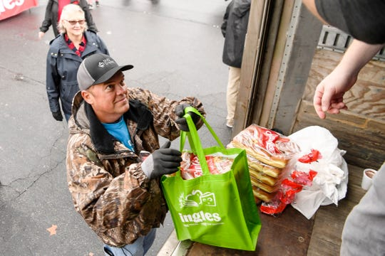 Fred Moore, a volunteer from Duke Energy, places bread rolls into a bag as more than 13,000 meals are distributed to clients of Eblen Charities with Ingles employees at the South Forest Shopping Center on Hendersonville Road November 27, 2019.