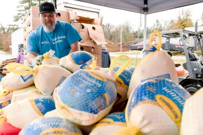 Volunteer Chris Polhamus stacks turkeys at the South Forest Shopping Center on Hendersonville Road November 27, 2019.