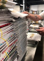 Columnist John Boyle says the Citizen Times is still a vital company, but it is one that needs reader support to stay alive. Here a worker puts together the big Thanksgiving Day paper.