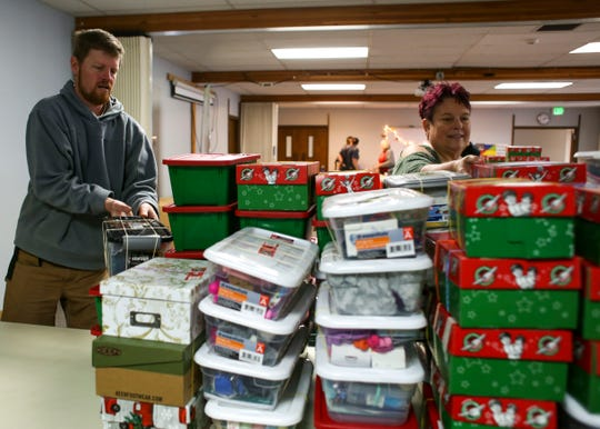 Operation Christmas Child volunteers sort shoeboxes filled with school supplies, hygiene items and toys at Kitsap Baptist Church in Poulsbo.