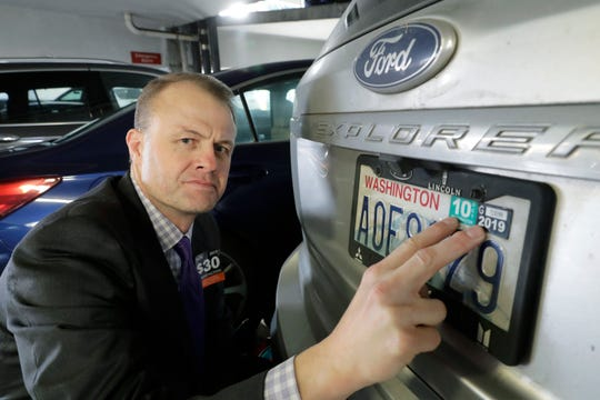 Tim Eyman, a career anti-tax initiative promoter, poses for a photo with the expired car registration tabs on his SUV, Tuesday, Nov. 26, 2019.