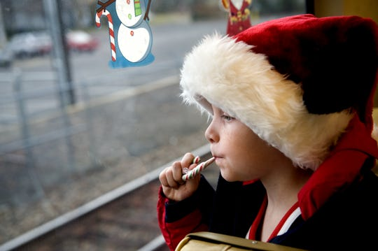A child rides on PATCO's Silver Sleigh, a specially decorated train with Christmas music playing and Santa on board.