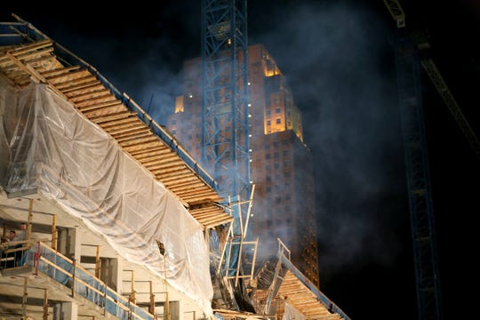Concrete dust rises into the air as authorities respond and search for a missing worker following a building collapse at a construction site, Monday, Nov. 25, 2019, at the intersection of Fourth and Elm streets in downtown Cincinnati. Turner Construction announced that four injured workers were released from the hospital late Monday night, but search and rescue crews worked through the night in search of one missing worker.