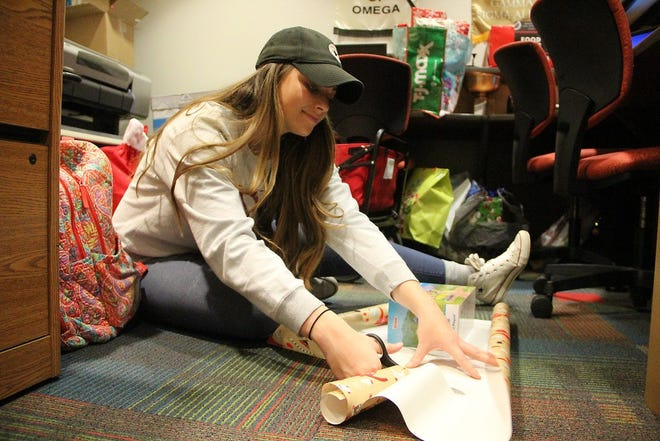 Anna Kail, former student employee in the office of Student Affairs, helps wrap gifts for the Help an Elf program in December 2018.