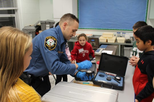 ALT students Madison Slater, Joseph Guerra, Charlotte Berez and Darrin Chen watch closely as Detective Joseph Casorio from the Warren Township Police Department explains how to dust for fingerprints.