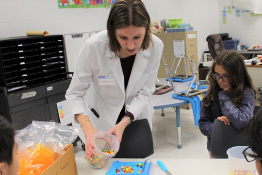 Dr. Renee Lippman, a pharmacologist, engages in a mock prescription preparation with skittles as ALT grade 4 student, Ava Baxter pays close attention.