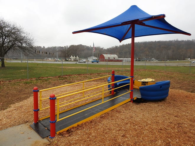 The Sway-Fun Glider at Hopewell School allows wheelchairs to be driven up a ramp and placed in the center. Students can sit in benches and rock back and forth or be pushed so all can play together.