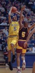 Michigan guard Jalen Rose  drives against Central Michigan's Torrey Mills on Monday, Dec. 20, 1993, at Crisler Arena.