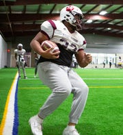 River Rouge running back De'Andre Bulley runs practice drills with teammates in Melvindale, Tuesday, Nov. 26, 2019.
