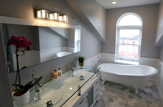 A top-floor dormer gives the ceiling shape to this owners' bath. It pairs a vintage claw-foot tub with a very contemporary light fixture and glass-topped double vanity. This Brush Park home was photographed on Tuesday, November 26, 2019.