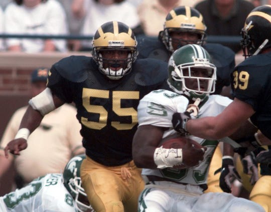 Michigan's Dhani Jones (55) moves in to make a hit on MSU's Sedrick Irvin (33) on Sept. 26, 1998, in Ann Arbor.