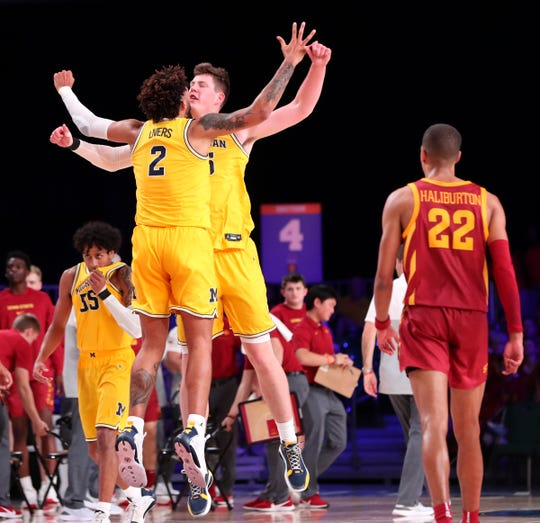 Michigan's Isaiah Livers and center Jon Teske celebrate in front of Iowa State guard Tyrese Haliburton during the 83-76 win over Iowa State in the Battle 4 Atlantis tournament on Wednesday, Nov. 27, 2019, in Paradise Island, Bahamas.